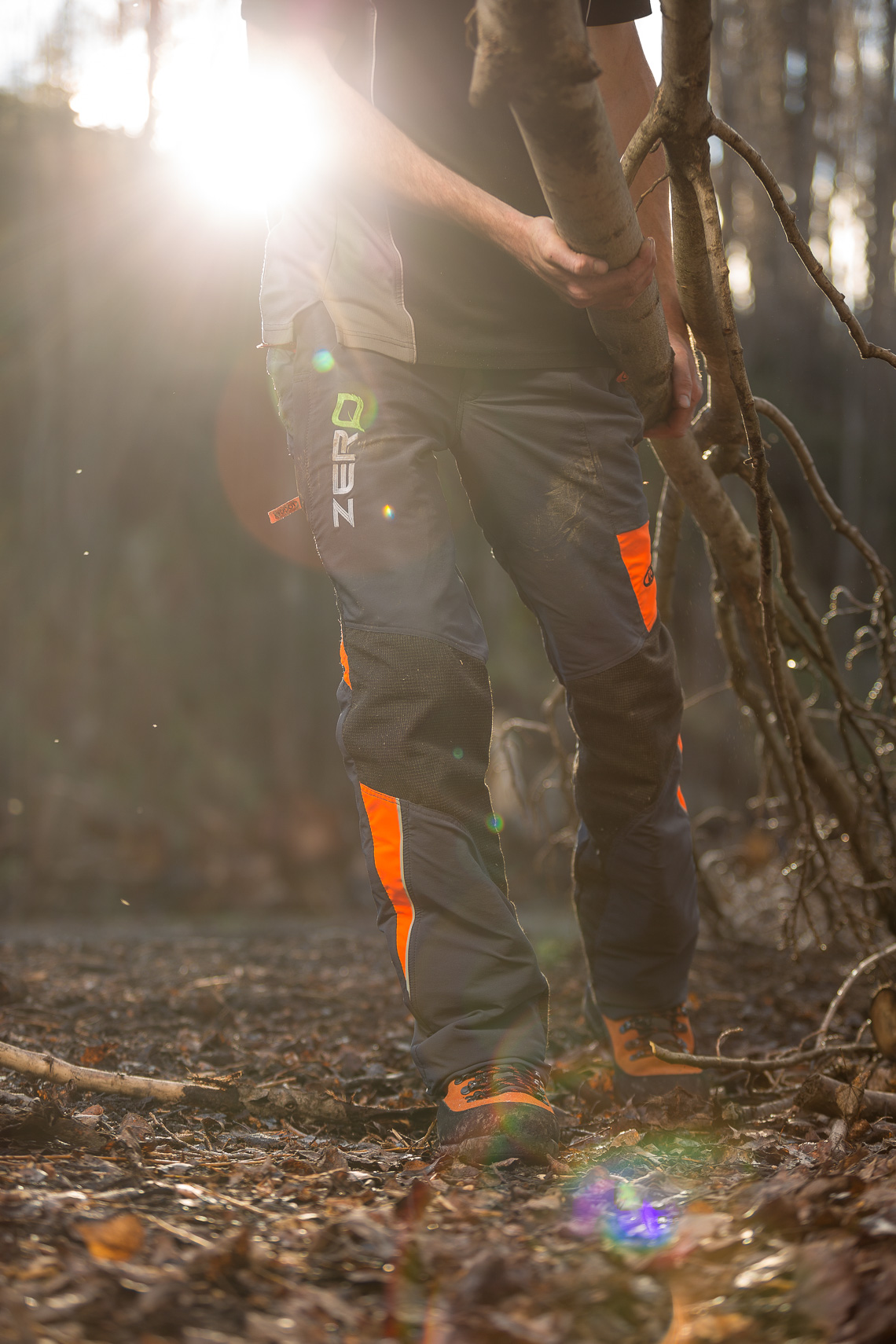 Arborist dragging felled branches wearing safety gear backlit with solar flare by Paul Green Photography