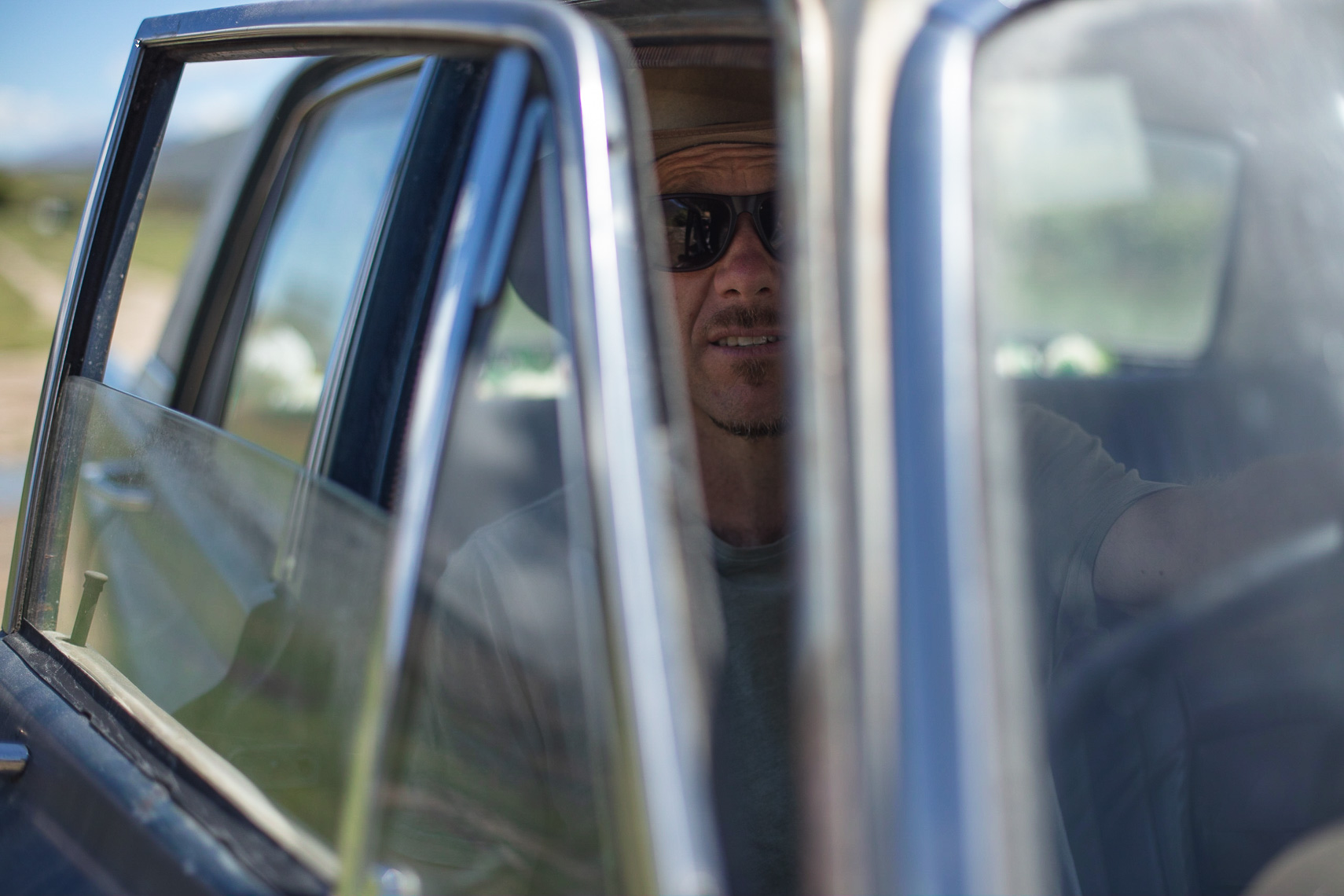 Man smiling while sitting in drivers seat of his vintage ford falcon by Paul Green Photographer