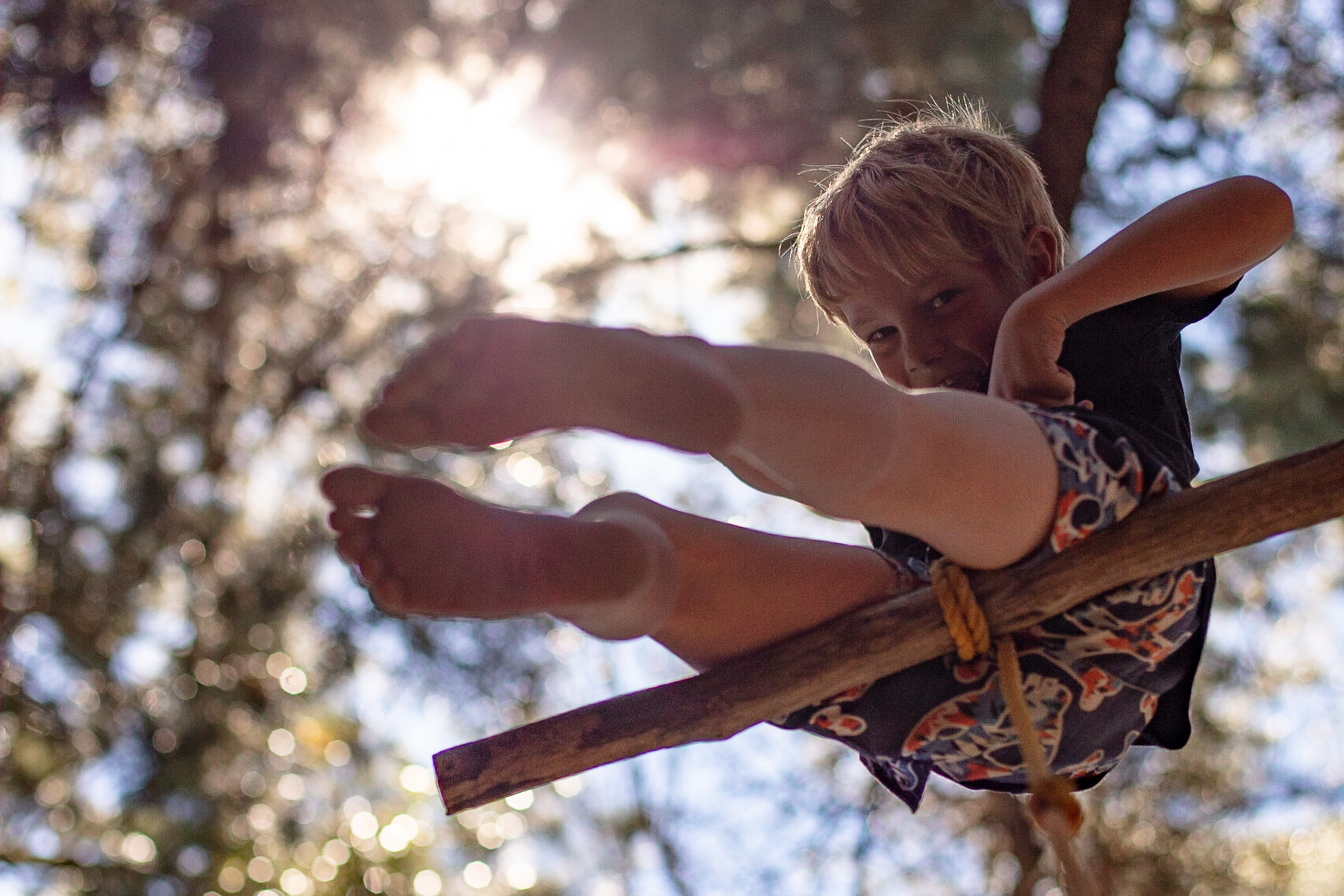 Young boy swinging on tree rope backlit by the sun through leaves by Paul Green Photography