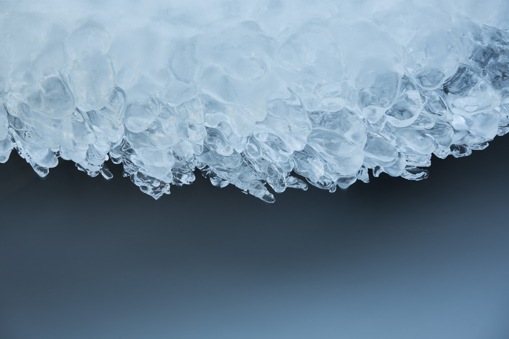 Close up of ice and flowing water in frozen river by Paul Green Photographer