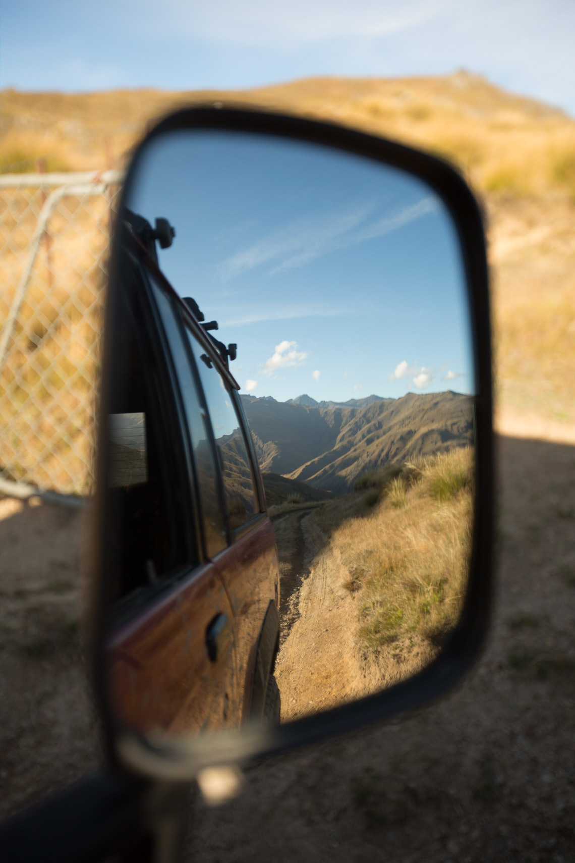 The road less travelled. The view in the mirror of a 4WD in Central Otago high country by Paul Green Photographer