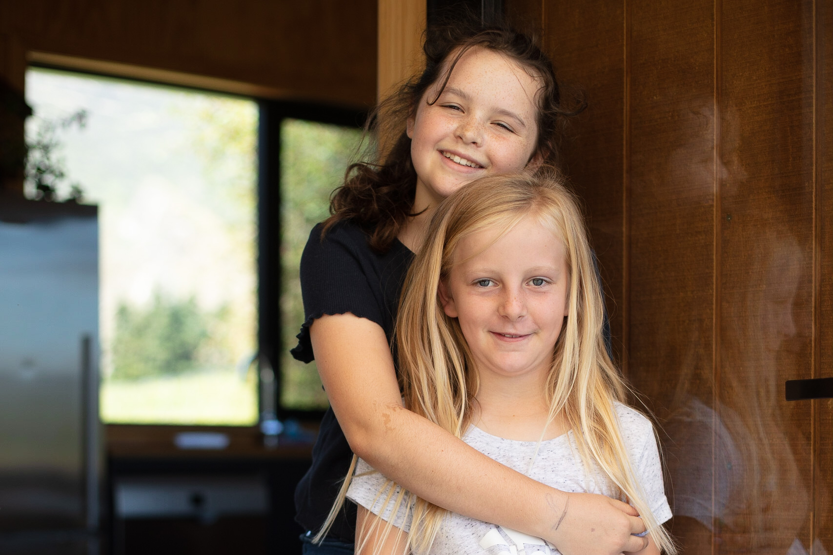 2 young girlfriends hug while smiling for the camera by Paul Green Photographer